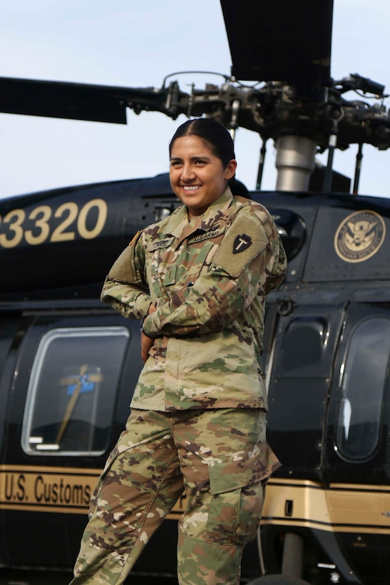 Pilot poses in front of helicopter.