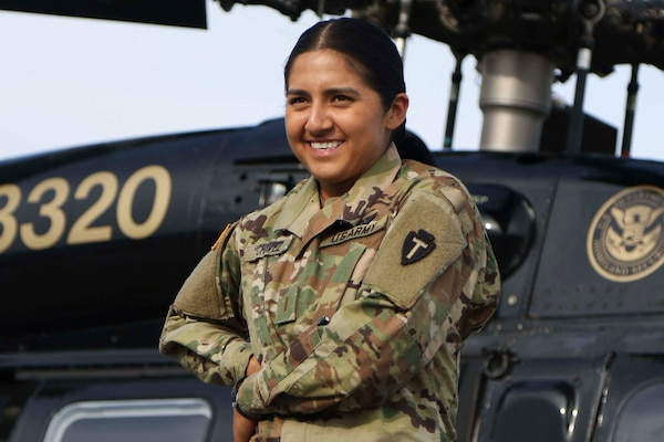 Army 2nd Lt. Liliana Chavez poses in front of a helicopter at McAllen International Airport, Texas, April 24, 2018. Chavez, who grew up in humble circumstances, today flies UH-60 Black Hawk and UH-72A Lakota helicopters for the Texas Army National Guard. Army photo by 1st Lt. Nadine Wiley De Moura