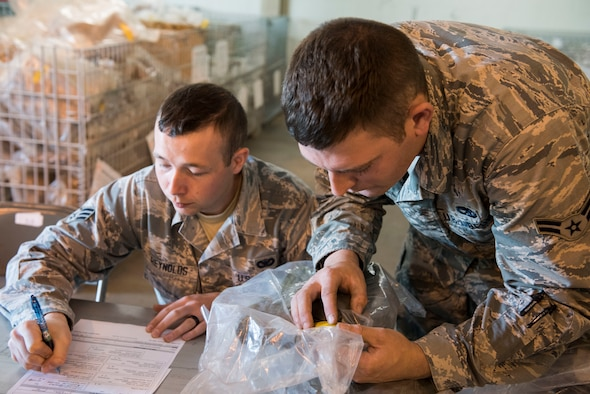 Senior Airman James Reynolds III (left), a 167th medical technician, works with Airman 1st Class Paul Sexton, a 167th aerospace propulsion mechanic, to pass out gear in a deployment mobility line at the 167th Airlift Wing, June 8, 2018. The wing plans to exercise some unused skills during a deployment exercise to Alpena, Mich., June 9-14. (U.S. Air National Guard photo by Tech. Sgt. Jodie Witmer)