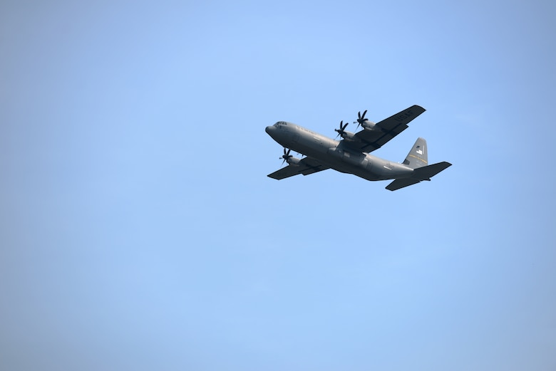 A C-130J aircraft flies in the sky going from right to left just after takeoff