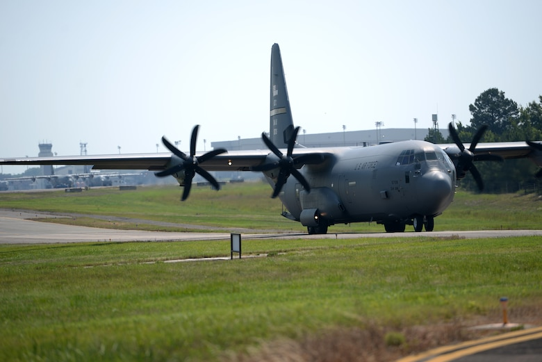 A C-130J Aircraft is taxing from left to right with the flight line behind it.