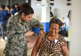 An Air Force medic gives a woman a shot.