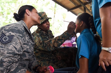A U.S. Air Force troop paints the face of a girl.