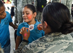 A U.S. Air Force member paints the face of a girl.