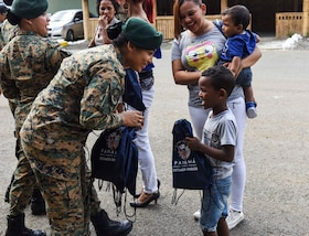 A Panama official passes bags out to children.