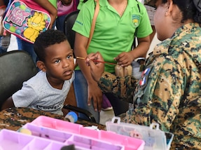 A uniformed official paints the face of a child