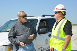 """Burton """"Burt"""" Moore, right, with the Savannah District, U.S. Army Corps of Engineers, discusses beach renourishment on Tybee Island, Georgia, with Joe Wilson, that town's director of public works. Moore oversees beach renourishments as part of his duties as the dredging manager for the Savannah District. In the spring of 2018, the Savannah District undertook the task of renourishing parts of Tybee's beach eroded by Hurricane Matthew in 2016. The $4.3 million contract took approximately 250,000 cubic yards of pristine beach sand from a """"borrow site"""" about a mile offshore and placed in onto specified areas of the beach. Beach renourishment helps protect the city from future storms. (U.S. Army Corps of Engineers photo by Billy Birdwell.)"""