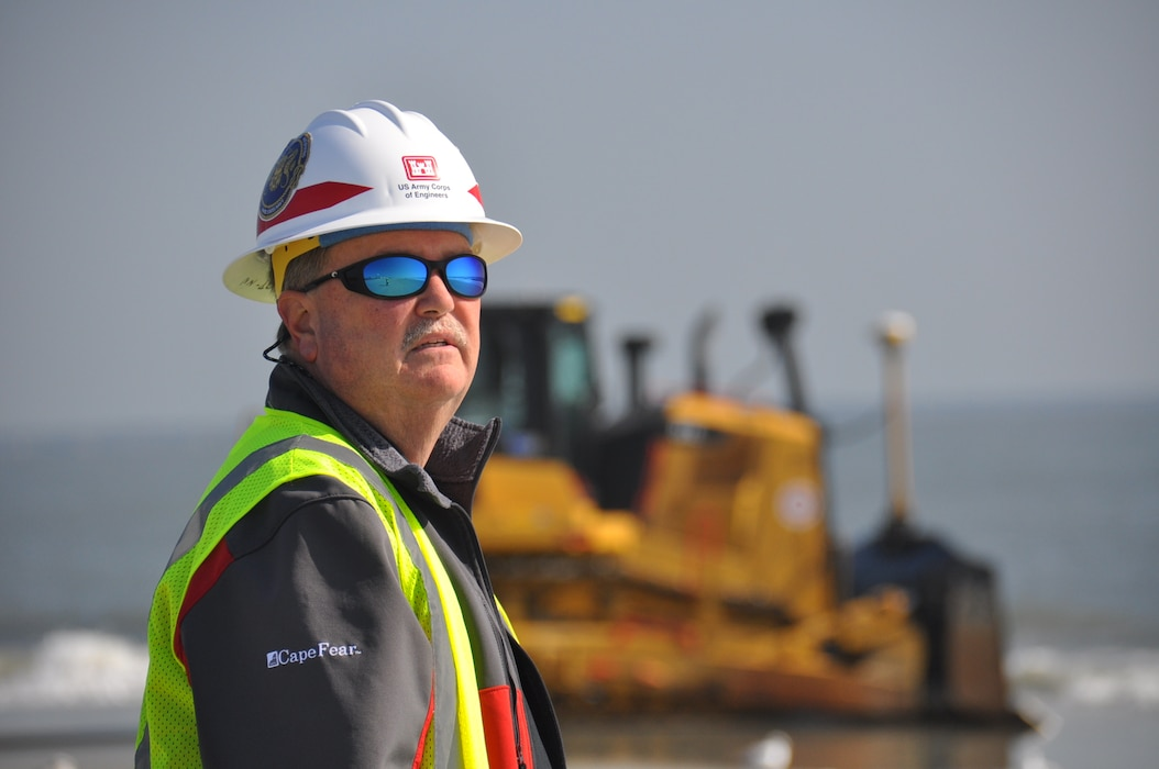 "Burton ""Burt"" Moore, Chief of the Dredging Section of the Savannah District, U.S. Army Corps of Engineers, surveys the beach renourishment at Tybee Island, Georgia. Moore oversees the work to repair beach erosion caused by Hurricanes Matthew and Irma in 2016 and 2017. Renourishing the beach will help mitigate damage from future storms striking the small Georgia resort town. The Corps of Engineers awarded the work contract to Great Lakes Dredge and Dock Company. Tybee Island sits adjacent to the Savannah harbor shipping channel, a federal navigation project. The Corps of Engineers continues its Savannah Harbor Expansion Project to deepen the entire harbor from its current 42-foot depth to 47 feet. Dredging crews completed the outer harbor, also known as the outer channel, deepening in the spring of 2018. (U.S. Army Corps of Engineers photo by Billy Birdwell.) (Photos taken on April 11, 2018.)"