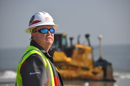 """Burton """"Burt"""" Moore, Chief of the Dredging Section of the Savannah District, U.S. Army Corps of Engineers, surveys the beach renourishment at Tybee Island, Georgia. Moore oversees the work to repair beach erosion caused by Hurricanes Matthew and Irma in 2016 and 2017. Renourishing the beach will help mitigate damage from future storms striking the small Georgia resort town. The Corps of Engineers awarded the work contract to Great Lakes Dredge and Dock Company. Tybee Island sits adjacent to the Savannah harbor shipping channel, a federal navigation project. The Corps of Engineers continues its Savannah Harbor Expansion Project to deepen the entire harbor from its current 42-foot depth to 47 feet. Dredging crews completed the outer harbor, also known as the outer channel, deepening in the spring of 2018. (U.S. Army Corps of Engineers photo by Billy Birdwell.) (Photos taken on April 11, 2018.)"""