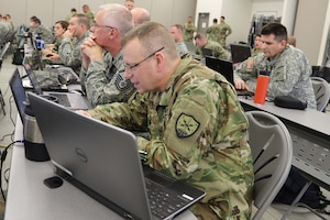 Soldiers and airmen work at laptop computers.