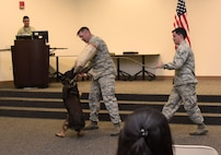 U.S. Air Force Staff Sgts. William Herron and Matthew Ratchford, 81st Security Forces Squadron military working dog handlers, and Toki, 81st SFS MWD, participate in a ceremonial final bite during a retirement ceremony at the Roberts Consolidated Aircraft Maintenance Facility at Keesler Air Force Base, Mississippi, June 8, 2018. Toki retired with over 10 years of military service and following his retirement Ratchford will be adopting him. (U.S. Air Force photo by Kemberly Groue)