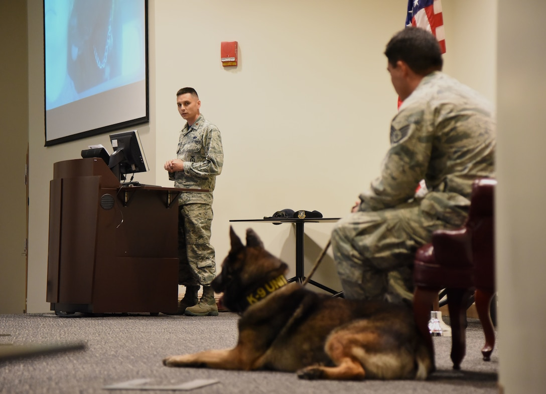 U.S. Air Force Maj. Jonathon Murray, 81st Security Forces Squadron commander, delivers remarks about Staff Sgt. Matthew Ratchford, 81st SFS military working dog handler, and his MWD, Toki, during a retirement ceremony at the Roberts Consolidated Aircraft Maintenance Facility at Keesler Air Force Base, Mississippi, June 8, 2018. Toki retired with over 10 years of military service, which included four deployments that included the one deployment Ratchford and Toki served together. (U.S. Air Force photo by Kemberly Groue)