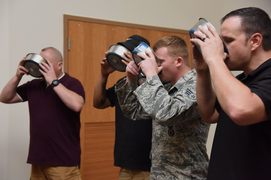 Members from the 81st Security Forces Squadron participate in a ceremonial toast to Toki, 81st SFS military working dog, for his retirement ceremony at the Roberts Consolidated Aircraft Maintenance Facility at Keesler Air Force Base, Mississippi, June 8, 2018. Toki retired with over 10 years of military service which included four deployments. (U.S. Air Force photo by Kemberly Groue)