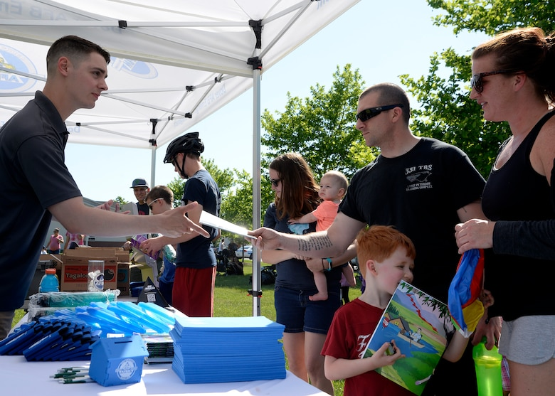 Senior Airman James Perry, 436th Civil Engineer Squadron emergency management apprentice, distributes disaster preparedness items to families May 24, 2018, during a hurricane block party in base housing on Dover Air Force Base, Del. The event was held to inform base residents on the hazards of being stationed on the coast during storm season. (U.S. Air Force photo/Tech. Sgt. Matt Davis)
