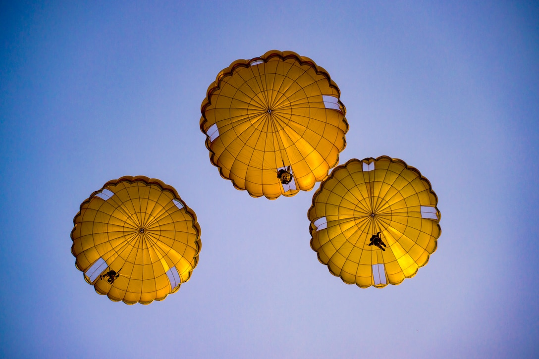 Three yellowish parachutes, shown from below, descend in a blue sky.