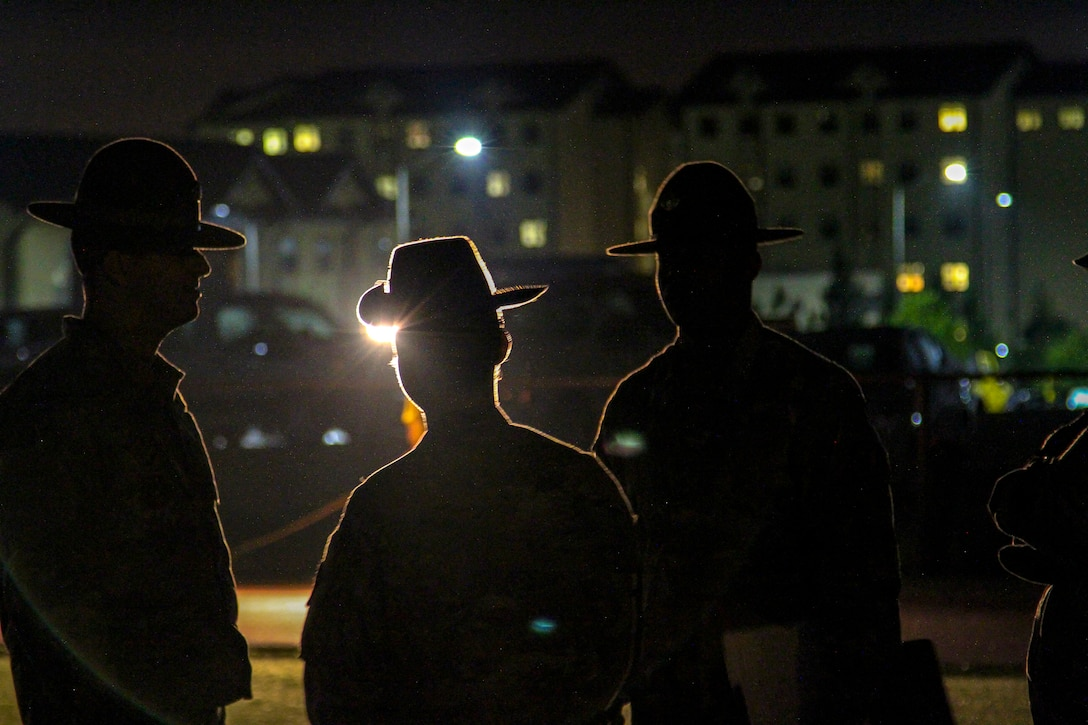 Three sergeants, shown in silhouette, look across a field toward a building at night.