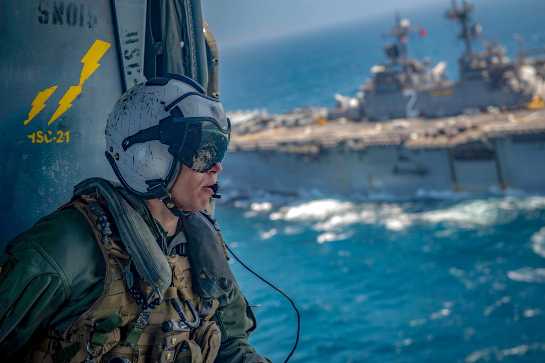 A sailor looks out over blue water and a passing ship while aboard a helicopter.