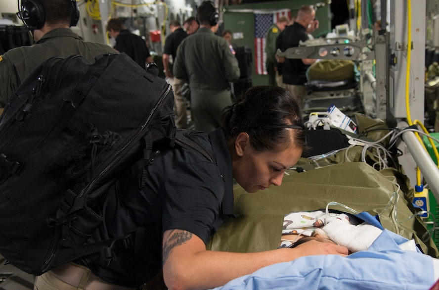 U.S. Army Capt. Argelia Felix-Camacho, registered nurse, San Antonio Military Medical Center Burn Team, consoles a patient during an aeromedical evacuation mission from Guatemala to Galveston, Texas, June 6, 2018. A U.S. Air Force C-17 Globemaster III from the Mississippi Air National Guard's 172nd Airlift Wing transported six injured children and their guardians to Galveston, Texas, for medical treatment at Shriners Hospital for Children. A joint medical team from the Mississippi Air National Guard's 183rd Air Evacuation Squadron and Joint Base San Antonio, Texas, provided en route medical treatment during the flight (U.S. Air Force photo by Master Sgt. Keyonna Fennell)
