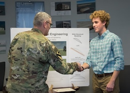 Nathan Weins, High School Intern with MED September through December 2017, is congratulated by Middle East District Commander Col. Stephen Bales, following his end of semester presentation about a bridge he designed.