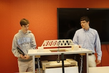 High School Intern Josh Dalton and Structural Engineer and High School Intern Program Coordinator Nathan Fox, prepare for the bridge break that will determine the weight-bearing capability of his design.