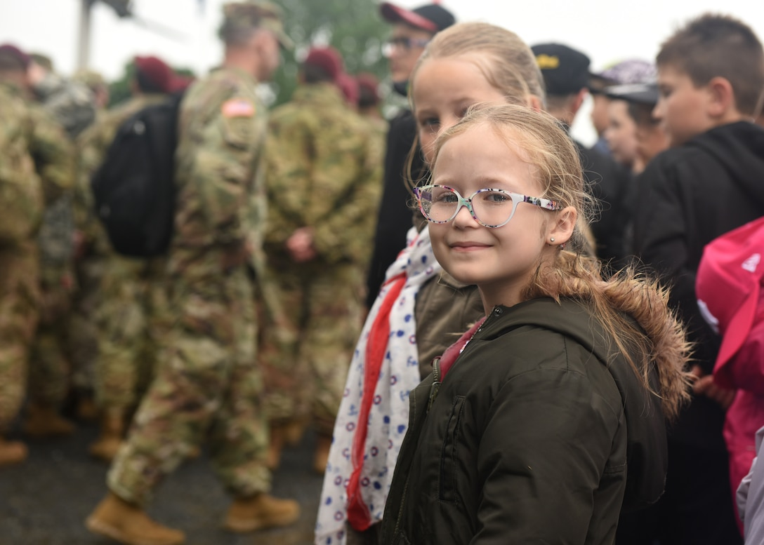A person observes military members during a celebration.