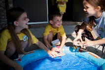 Children operate their arts and crafts projects in a small pool of water during the base chapel's Vacation Bible School, June 8, 2018, at Moody Air Force Base, Ga. VBS is designed to assist children in building resiliency to the stressors many military families face. More than 95 children and 65 volunteers attended this year's VBS. (U.S. Air Force photo by Senior Airman Daniel Snider)