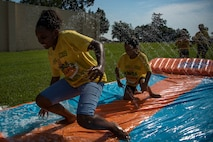 Children slide across a water slide during the base chapel's Vacation Bible School, June 8, 2018, at Moody Air Force Base, Ga. VBS is designed to assist children in building resiliency to the stressors many military families face. More than 95 children and 65 volunteers attended this year's VBS. (U.S. Air Force photo by Senior Airman Daniel Snider)
