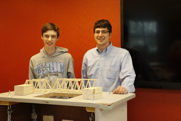Intern Josh Dalton with High School Intern Program and Structural Engineer Nathan Fox following Dalton's end of semester bridge break test. Fox assists interns in exploring engineering disciplines and building their self-confidence.