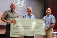 Douglas Wadsworth (left), chief of staff, Marine Corps Base Hawaii (MCBH), poses for a photo with retired retired U.S. Navy Adm. Steve Abbot (middle), the president of Navy-Marine Corps Relief Society (NMCRS) while holding a check during the NMCRS Active Duty Fund Drive award ceremony, at the base theater, MCBH, June 11, 2018. The NMCRS provides financial relief to active duty and retired Marines and Sailors as well as their eligible surviving family members through interest-free loans and grants. (U.S. Marine Corps photo by Lance Cpl. Matthew Kirk)