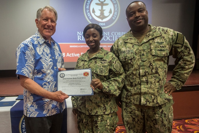 Retired U.S. Navy Adm. Steve Abbot, the president of Navy-Marine Corps Relief Society (NMCRS), presents sailors with Naval Personnel Support Detachment Pearl Harbor an award for second highest contributions during the NMCRS Active Duty Fund Drive award ceremony, at the base theater, Marine Corps Base Hawaii, June 11, 2018. The NMCRS provides financial relief to active duty and retired Marines and Sailors as well as their eligible surviving family members through interest-free loans and grants. (U.S. Marine Corps photo by Lance Cpl. Matthew Kirk)