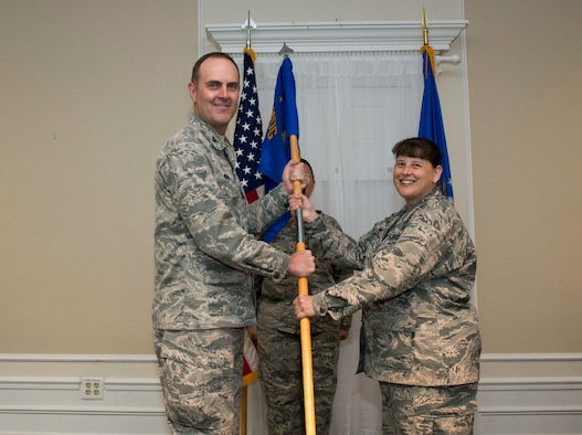U.S. Air Force Col. Brian Wyrick, 20th Medical Group (MDG) commander, left, passes the 20th Medical Support Squadron (MDSS) guidon to Lt. Col. Melissa Meister, 20th MDSS commander, at Shaw Air Force Base, S.C., June 12, 2018.