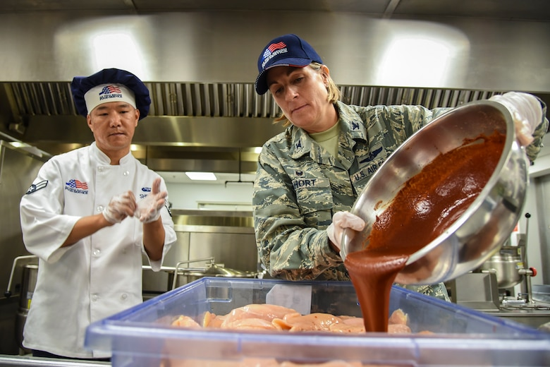 Col. Jennifer Short, right, 23d Wing (WG) commander, pours sauce onto chicken during an immersion tour, June 11, 2018, at Moody Air Force Base, Ga. Short and Chief Master Sgt James Allen, 23d WG command chief  toured the Georgia Pines Dining Facility and the Information Learning Center to gain a better understanding of their overall mission, capabilities and comprehensive duties. (U.S. Air Force photo by Airman 1st Class Eugene Oliver)