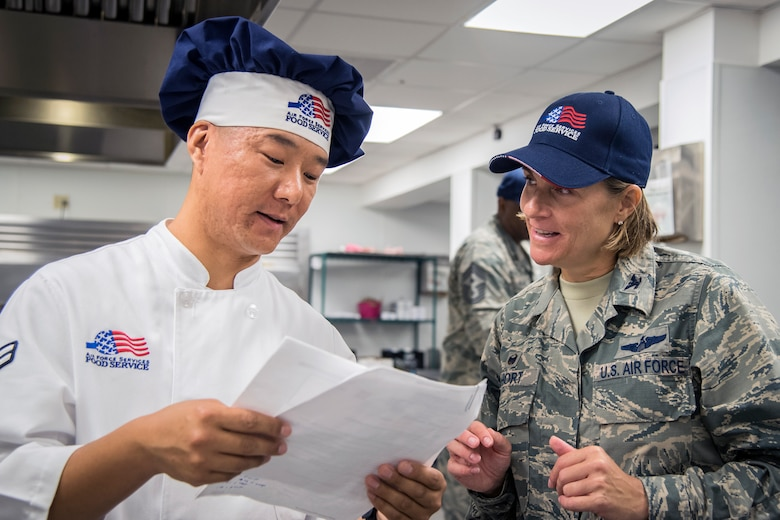 Airman 1st Class Pema Sherpa, left, 23d Force Support Squadron services journeyman, teaches a recipe to Col. Jennifer Short, 23d Wing (WG) commander, during an immersion tour, June 11, 2018, at Moody Air Force Base, Ga. Short and Chief Master Sgt James Allen, 23d WG command chief, toured the Georgia Pines Dining Facility and the Information Learning Center to gain a better understanding of their overall mission, capabilities and comprehensive duties. 	(U.S. Air Force photo by Airman 1st Class Eugene Oliver)