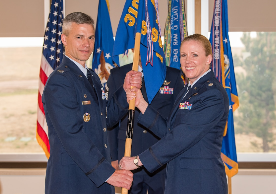 Col. Stephen Slade, 310th Operations Group commander, receives the 19th Space Operations Squadron guidon from Lt. Col. Karen Slocum as she relinquishes command of the squadron, June 3, 2018.
