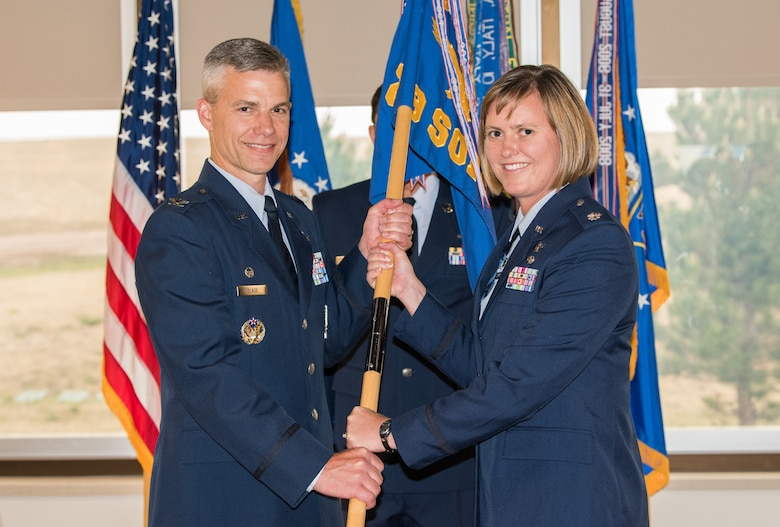 Col. Stephen Slade, 310th Operations Group commander, passes the 19th Space Operations Squadron guidon to Lt. Col. Beth Stargardt as she takes command of 19 SOPS, June 3, 2018.
