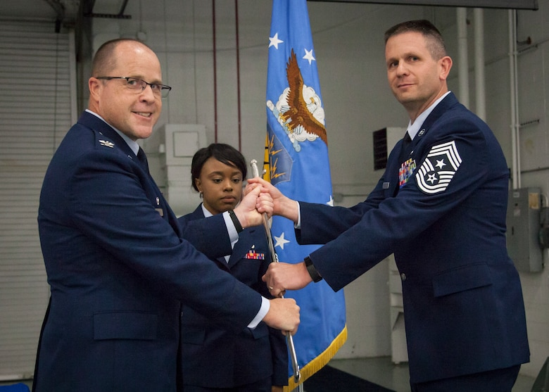 U.S. Air Force Col. James Locke, wing commander of the 128th Air Refueling Wing, hands the Chief's Saber to Command Chief Master Sgt. Thomas Fredrickson during a change of authority ceremony Oct. 14, 2017.