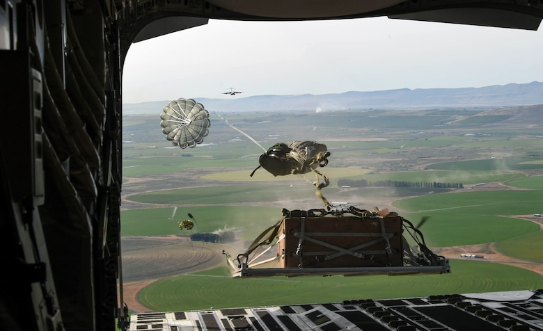 A container delivery system bundle drops out of a C-17 Globemaster III during Exercise Rainier War at the Rainier Drop Zone near Moses Lake, Wash., June 6, 2018. Eighteen C-17s and three KC-135 Stratotankers from McChord Field, other Air Mobility Command bases and Australia participated in Rainier War. (U.S. Air Force photo by Senior Airman Tryphena Mayhugh)