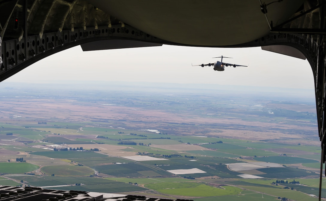 A C-17 Globemaster III flies behind another C-17 during Exercise Rainier War near Moses Lake, Wash., June 6, 2018. During the exercise, 20 C-17s from the U.S. and Australia performed actual container delivery system (CDS) and heavy equipment airdrops at the Rainier Drop Zone near Moses Lake, and simulated improved CDS, CDS and high altitude low opening personnel airdrops throughout the western United States. (U.S. Air Force photo by Senior Airman Tryphena Mayhugh)