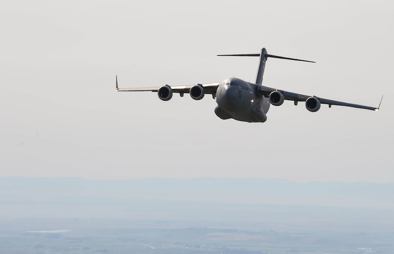 A C-17 Globemaster III flies during Exercise Rainier War to perform container delivery system bundle airdrops near Moses Lake, Wash., June 6, 2018. During the exercise, 20 C-17s from the U.S. and Australia performed actual container delivery system (CDS) and heavy equipment airdrops at the Rainier Drop Zone near Moses Lake, and simulated improved CDS, CDS and high altitude low opening personnel airdrops throughout the western United States. (U.S. Air Force photo by Senior Airman Tryphena Mayhugh)