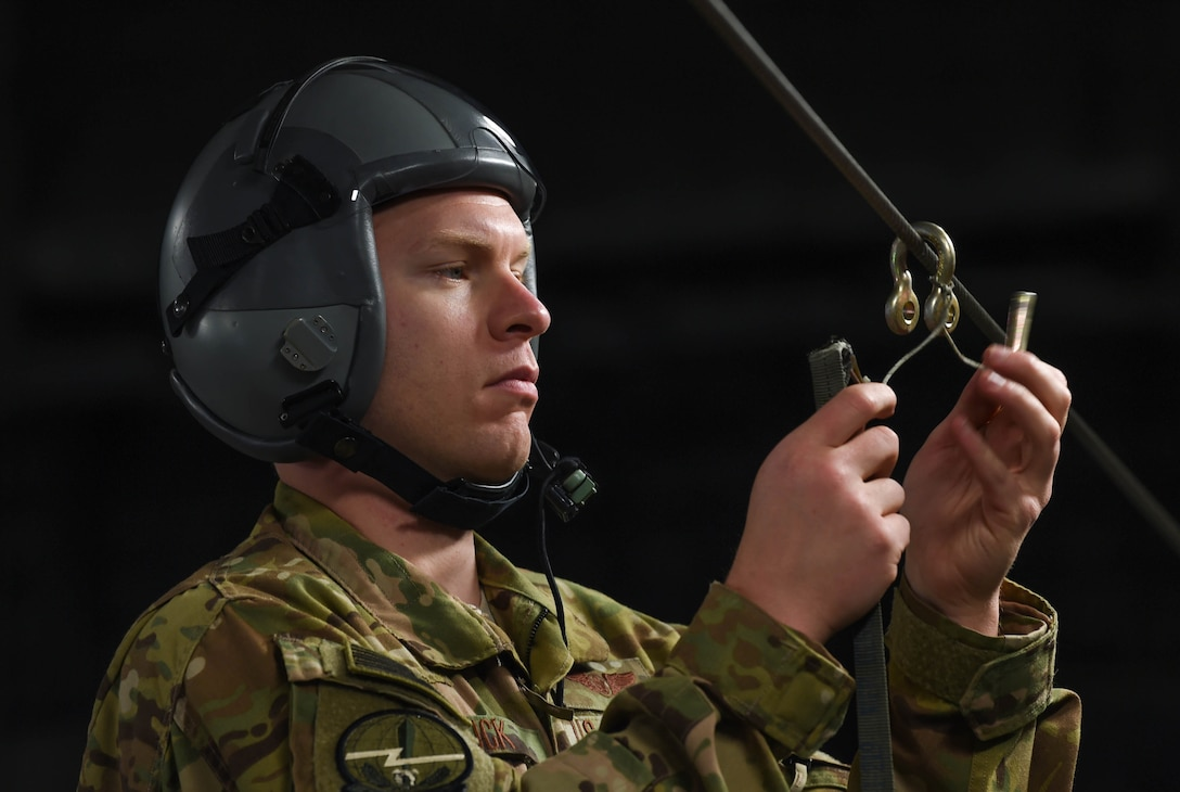 Staff Sgt. Matthew Duck, 7th Airlift Squadron loadmaster, unhooks a parachute cover after dropping two bundles out of a C-17 Globemaster III onto the Rainier Drop Zone during Exercise Rainier War near Moses Lake, Wash., June 6, 2018. During the exercise, 20 C-17s from the U.S. and Australia performed actual container delivery system (CDS) and heavy equipment airdrops at the Rainier Drop Zone near Moses Lake, and simulated improved CDS, CDS and high altitude low opening personnel airdrops throughout the western United States. (U.S. Air Force photo by Senior Airman Tryphena Mayhugh)