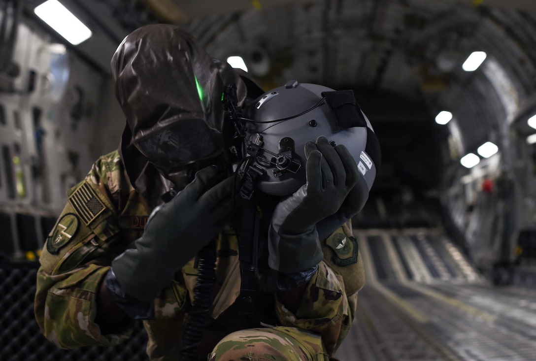 First Lt. Edmund Duvall, 7th Airlift Squadron pilot, removes an aircrew eye and respiratory protection system (AERPS) while flying in a C-17 Globemaster III during Exercise Rainier War near Moses Lake, Wash., June 6, 2018. The crew's ability to put on AERPS gear properly was one aspect they trained on during the exercise. (U.S. Air Force photo by Senior Airman Tryphena Mayhugh)