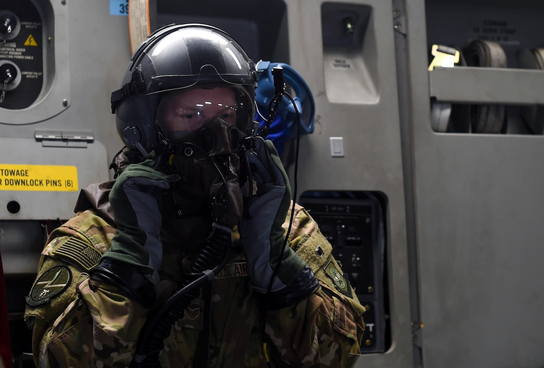 Staff Sgt. Matthew Duck, 7th Airlift Squadron loadmaster, tests the functionality of his aircrew eye and respiratory protection system while flying in a C-17 Globemaster III near Moses Lake, Wash., June 6, 2018. Duck was participating in Exercise Rainier War, which provided insights on how to better execute a tactical scenario for possible future conflicts. (U.S. Air Force photo by Senior Airman Tryphena Mayhugh)