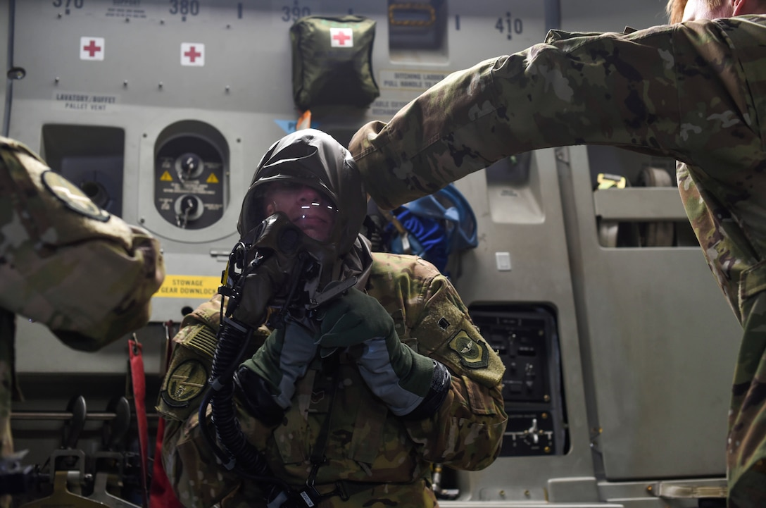 Staff Sgt. Matthew Duck, 7th Airlift Squadron loadmaster, removes an aircrew eye and respiratory protection system while flying in a C-17 Globemaster III during Exercise Rainier War near Moses Lake, Wash., June 6, 2018. The purpose of exercise was to highlight the C-17's capabilities to perform the Air Force's core competencies of rapid global mobility and precision engagement. (U.S. Air Force photo by Senior Airman Tryphena Mayhugh)