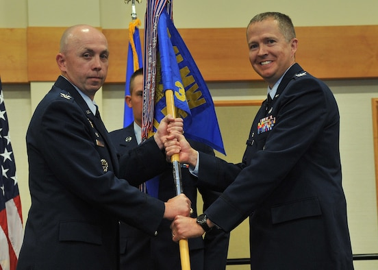 Col. Jeremy Hooper, right, accepts command of the 341st Medical Group from Col. Ron Allen, 341st Missile Wing commander, during an assumption of command ceremony June 12, 2018, at the Grizzly Bend at Malmstrom AFB, Mont. Guidon bearer Master Sgt. Josh Varner, 341st MDG first sergeant, looks on. (U.S. Air Force photo/John Turner)