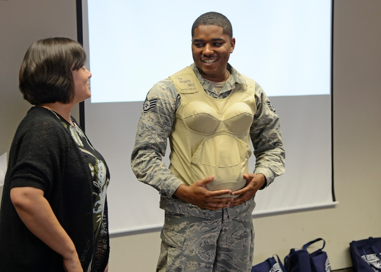Arlene Johnson, Family Advocacy outreach manager tries the empathy belly on a future father, Staff Sgt. Gregory Bolden, 31st Test and Evaluation Squadron, to simulate the weight that is carried during pregnancy. (U.S. Air Force photo by Laura Motes)