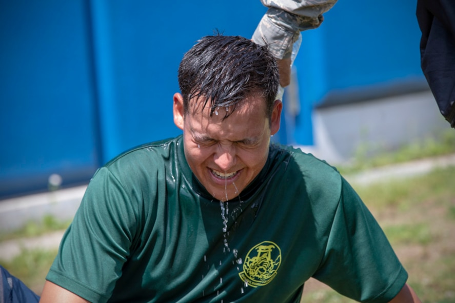 Airman 1st Class Matthew Byce, 374th Civil Engineer Squadron structural apprentice, gets drenched with a cold water after finished four-person relay during an Ability to Survive and Operate (ATSO) Rodeo