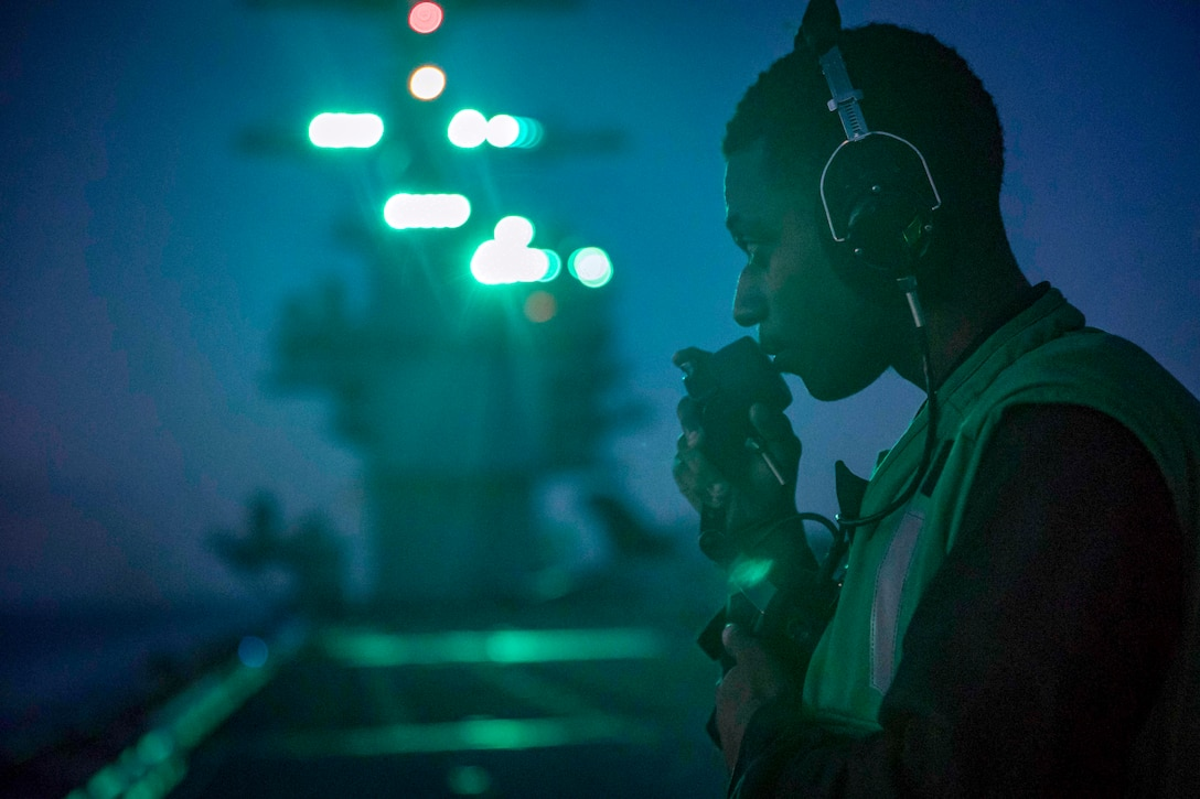 A sailor wearing headphones speaks into a device on a ship's deck, against a dark blue sky.