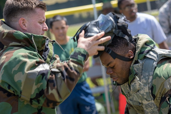 Maj. Logan Smith, left, 374th Civil Engineer Squadron operation flight commander, removes Senior Airman Felix Nunez, right, 374th CES electrical system technician, gas mask during an Ability to Survive and Operate (ATSO) Rodeo