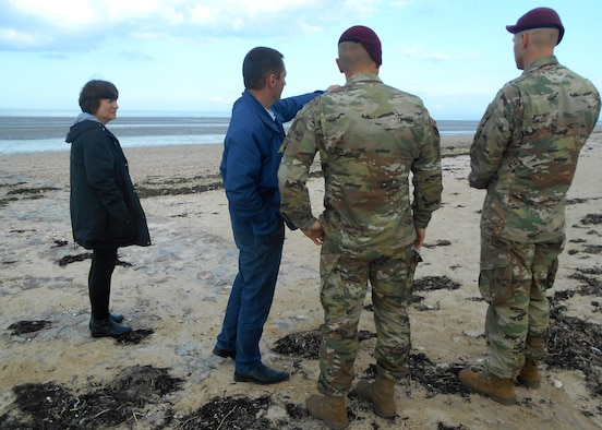 Service member speak to a local on a beach in Normandy, France.