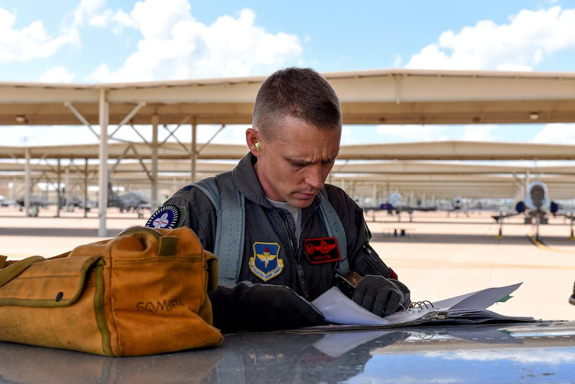 Lieutenant Colonel Mitchell Cok, 88th Fighter Training Squadron, recognized for Profession of Arms Center of Excellence Leadership Impact Award, goes over preflight check list before Introduction to Fighter Fundamentals training sortie at Sheppard Air Force Base, Texas, May 22, 2018 (U.S. Air Force/John Ingle)